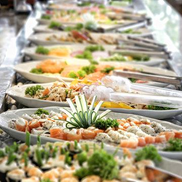 A shallow depth of field image looking along a sushi buffet bar