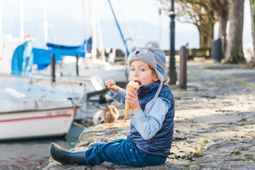 Adorable little boy eating ice cream outdoors on a cold weather