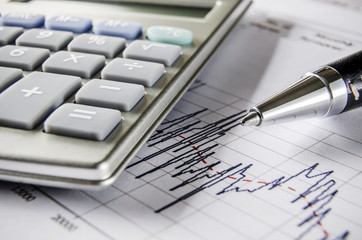 Stock exchange graph with calculator and pen