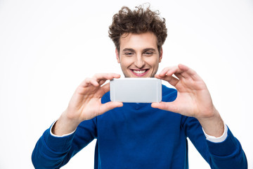 Smiling man making photo on smartphone over gray background