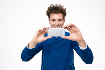 Happy man making photo on smartphone over gray background