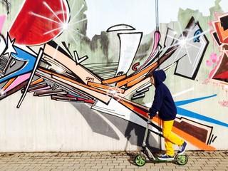Junge fährt Roller vor Graffiti