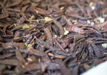 Portrait of many dried carob beans.