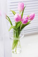 Beautiful pink tulips in glass vase on windowsill background