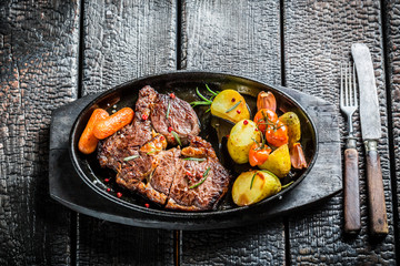 Roasted steak and vegetables with herbs on grill
