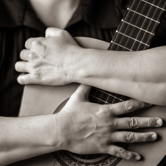Musician hands embracing a classic acoustic guitar
