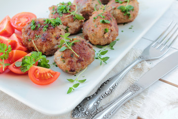 Meatballs with parsley and thyme herbs on a white plate