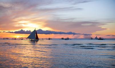 Sailing boat at beautiful colorful sunset