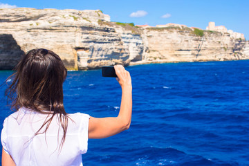 Girl taking pictures on a phone in Bonifacio, Corsica, France