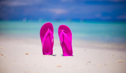 Pink vibrant beach flip flops on white sand on sea background