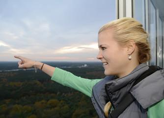 Junge Frau zeigt aus dem Fenster, Berlin, Deutschland