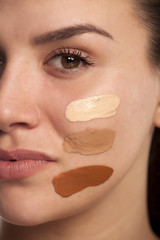 Face of woman with tree different tones of liquid foundation