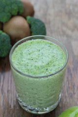 Glass full of apple, broccoli and kiwi milk smoothie.