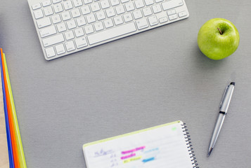 Office work space on grey desk with green apple