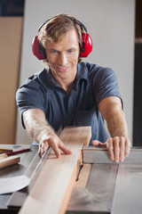 Carpenter Using Tablesaw To Cut Wooden Plank