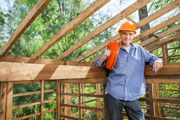 Confident Worker Holding Pipe In Wooden Cabin