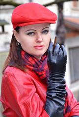Mujer elegante enntraje invernal rojo, fumando.