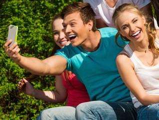 Sporty teenage friends in a park taking selfie