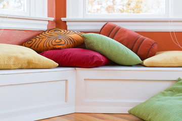 Window seat with cushions. Colorful and cheerful.