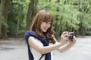A woman in a Kyoto park holding a camera, preparing to take pictures.