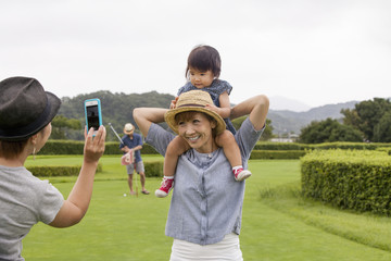Family on a golf course. A child on a woman's shoulders.