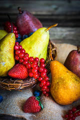 Pears with berries on wooden background