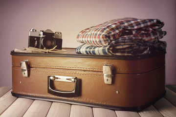 Vintage suitcase with clothes and camera