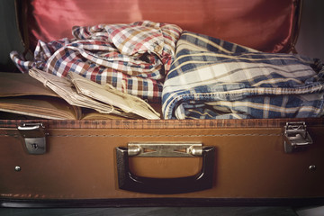 Vintage suitcase open with clothes and books close up