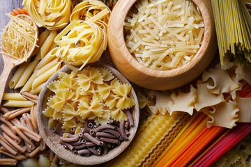 Different types of pasta with wooden bowls, macro view