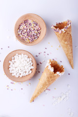 empty ice cream cones with colourful sprinkles