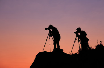 Silhouette of a photographers who shooting a sunset on the mount
