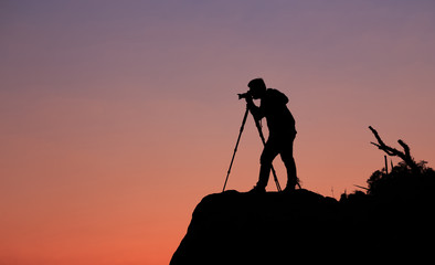 Silhouette of a photographer who shooting a sunset on the mounta