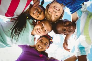 Portrait of happy children forming huddle