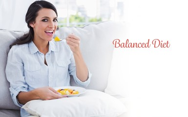 Happy woman sitting on the sofa eating fruit salad