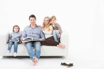 Happy family on the couch reading a book