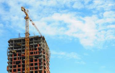 Building crane under construction site against blue sky