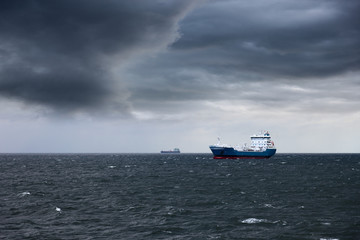 Dark cloudy stormy sky with ship and waves in the sea.