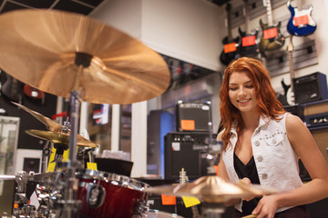 Spoed Foto op Canvas Muziekwinkel smiling musician playing cymbals at music store