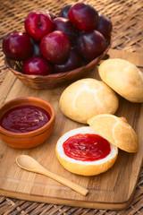 Plum jam spread on bun with plums in basket