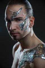Young handsome man with mosaic body art painting