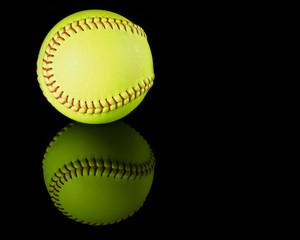 Softball on black reflective background.
