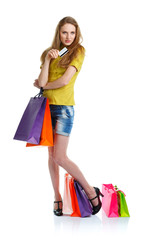 Happy caucasian woman with shopping bags and holding credit card