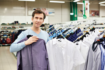 Man chooses shirt in shop