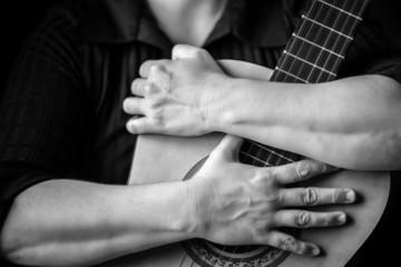 Hands hugging an acoustic guitar