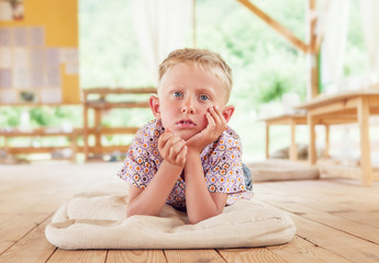 Bored boy lying on the wooden terrace on summer day