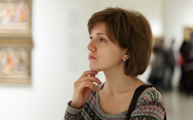 woman looking pictures in art gallery