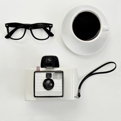 eyeglasses, coffee and instant camera
