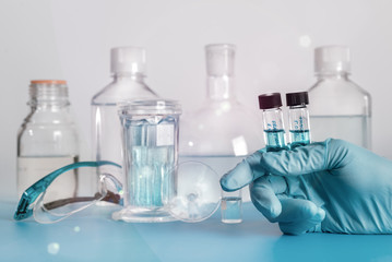 Two liquid samples in plastic vials in gloved hand