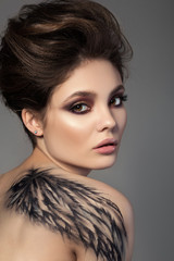 Portrait of young sensual brunette woman with black wing