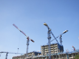Modern buildings under construction and cranes under blue sky